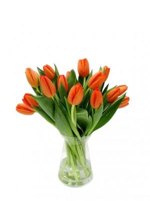 Tulipanes naranjas en jarrón de cristal